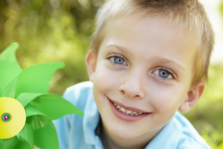 8 years: Young boy outdoors with windmill Stock Photo