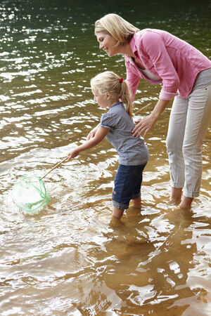 children pond: Mother and young daughter with fishing net