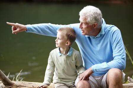 personas reunidas: Abuelo y nieto que se sientan por el lago Foto de archivo