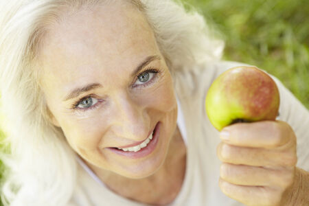 woman eating fruit: Senior woman eating apple outdoors Stock Photo