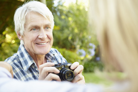 taking photograph: Senior couple taking photo outdoors Stock Photo