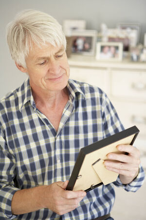 indoor photo: Senior man with photographs at home Stock Photo