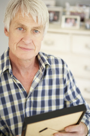 Senior man with photographs at home Stock Photo