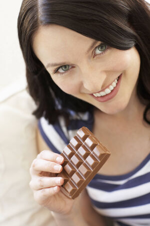 indulging: Woman eating chocolate Stock Photo
