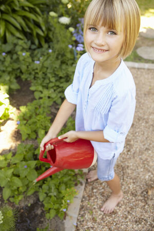young girl barefoot: Young girl watering garden