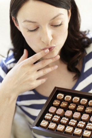 indulging: Woman eating chocolates Stock Photo