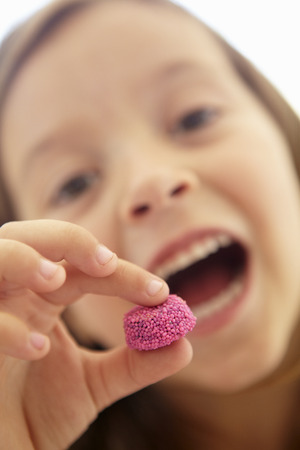 girl open mouth: Little girl eating candy