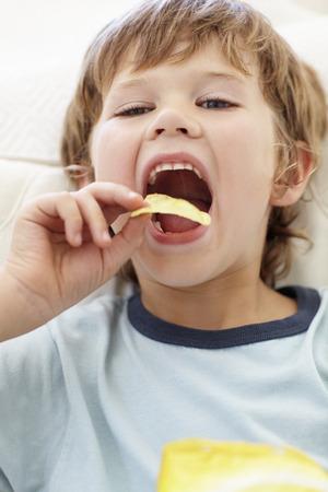 potato crisps: Young boy eating crisps
