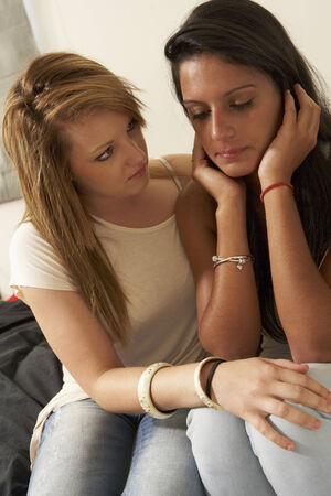 girl sit: Unhappy teenage girl with friend