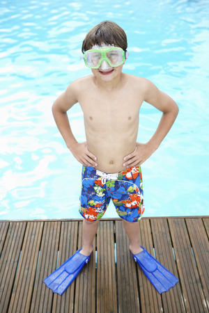 swimming shorts: Boy by outdoor swimming pool Stock Photo