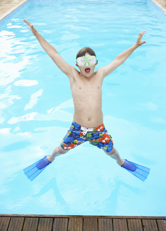 Boy jumping into outdoor swimming pool Stock Photo