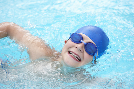 pool preteen: Boy swimming in outdoor pool