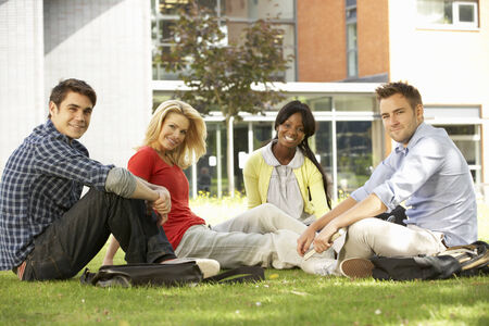 sitting on the ground: Mixed group of students outside college Stock Photo