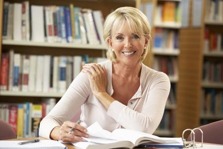 Estudiante mayor que trabaja en la biblioteca Foto de archivo - 33603731