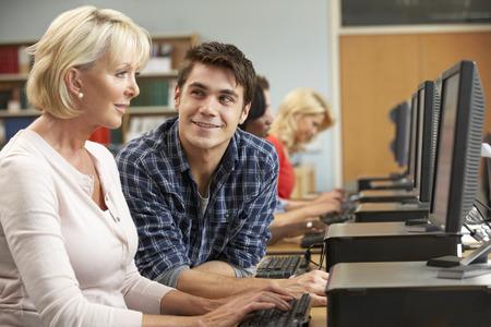 hombres jovenes: Los estudiantes que trabajan en las computadoras de la biblioteca Foto de archivo