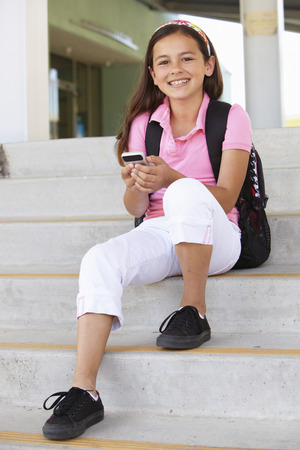 10 year old: Pre teen girl with phone at school Stock Photo