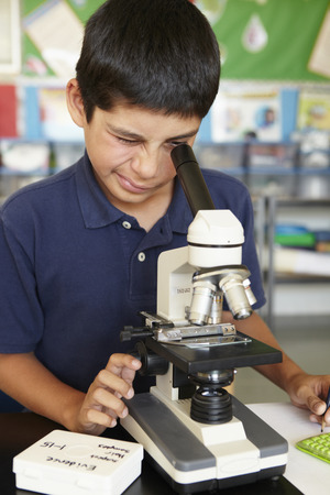 discovering: Boy in science class with microscope Stock Photo