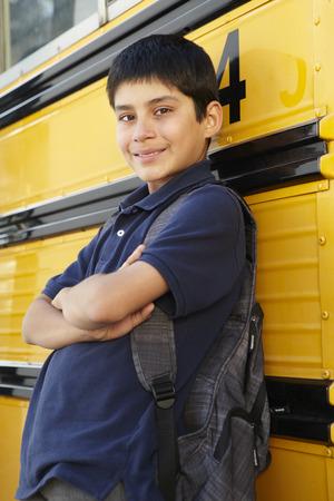 pre teen boy: Pre teen boy with school bus Stock Photo