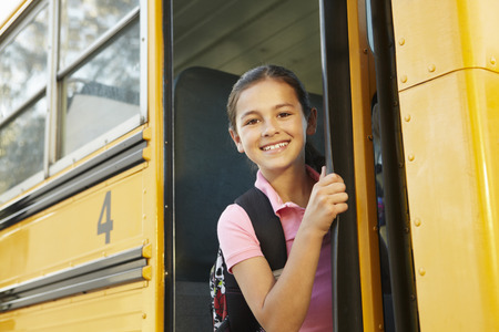 Pre teen girl getting on school bus photo