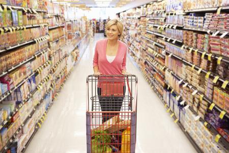 supermarket shelf: Woman shopping in supermarket Stock Photo