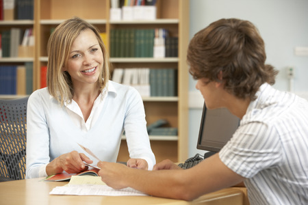 male teacher: College tutor with student Stock Photo