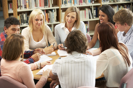 Students and tutor working in library Standard-Bild