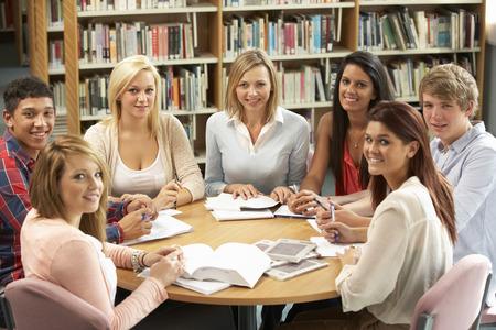 Studenten en privé-leraar die in bibliotheek werken