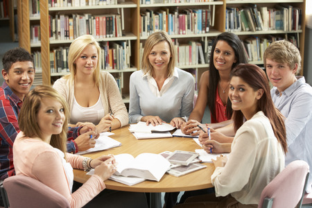 collaborating: Students and tutor working in library Stock Photo