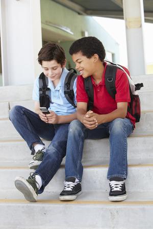 teen boys: Pre ragazzi adolescenti con telefono a scuola
