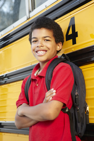 informal clothing: Pre teen boy with school bus Stock Photo