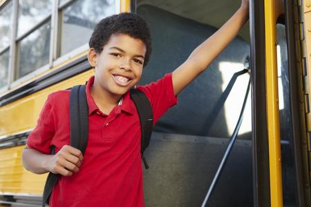 Pre teen boy getting on school bus photo