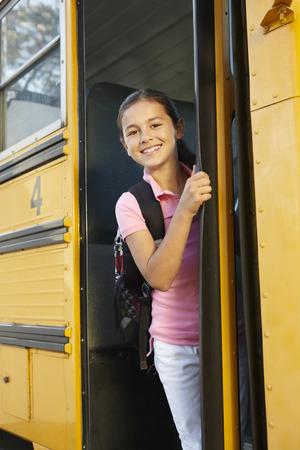 escuela primaria: Ni�a pre adolescente que consiguen en el autob�s escolar Foto de archivo