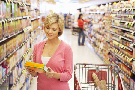 managing: Woman shopping in supermarket Stock Photo