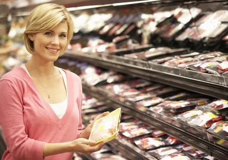 Woman shopping in supermarket Standard-Bild
