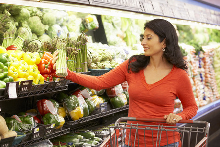 Woman shopping in supermarket Imagens