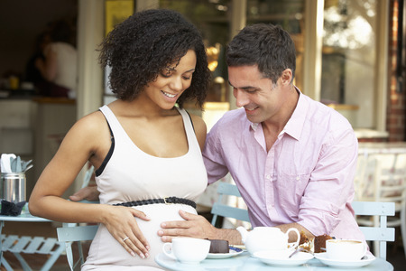 pregnant woman with husband: Expectant couple sitting outside caf� Stock Photo