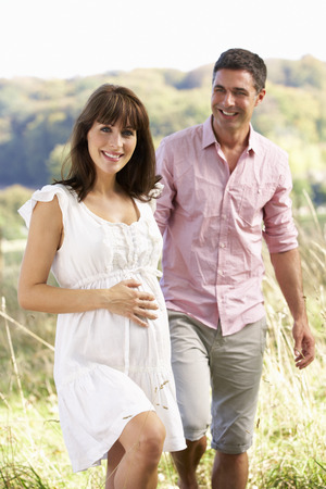 woman in field: Expectant couple outdoors in countryside