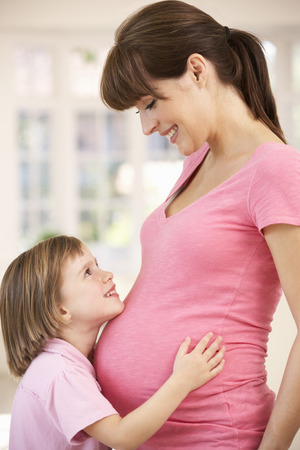 Pregnant woman with daughter photo