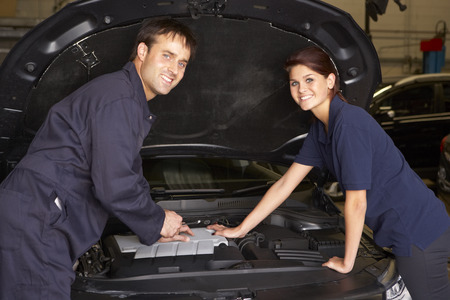 two car garage: Female trainee mechanic at work Stock Photo