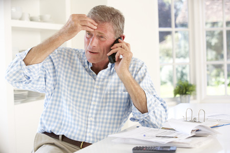 frustrated man: Retired man with household bills