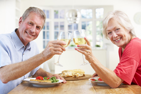 Retired couple enjoying meal at home photo