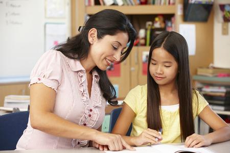 pre adult: Teacher and schoolgirl in class Stock Photo