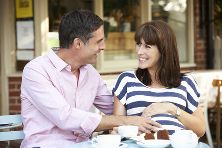 eating pastry: Expectant couple sitting outside café