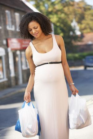 Zwangere vrouw met zware boodschappen Stockfoto