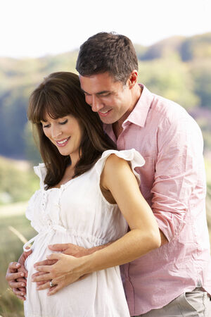 homme enceinte: Expectant couple en plein air dans la campagne