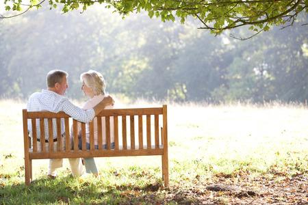 hugging couple: Senior couple sitting outdoors