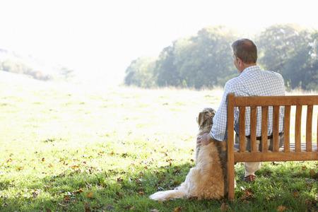 sitting man: Senior man sitting outdoors with dog Stock Photo