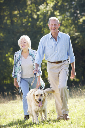 person walking: Senior couple walking dog