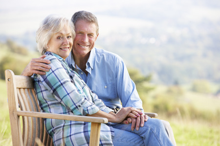 happily: Senior couple sitting outdoors