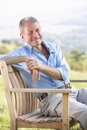man outdoors: Senior man sitting outdoors